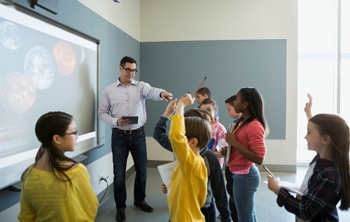 man with glasses teaching students using tablet and smartboard